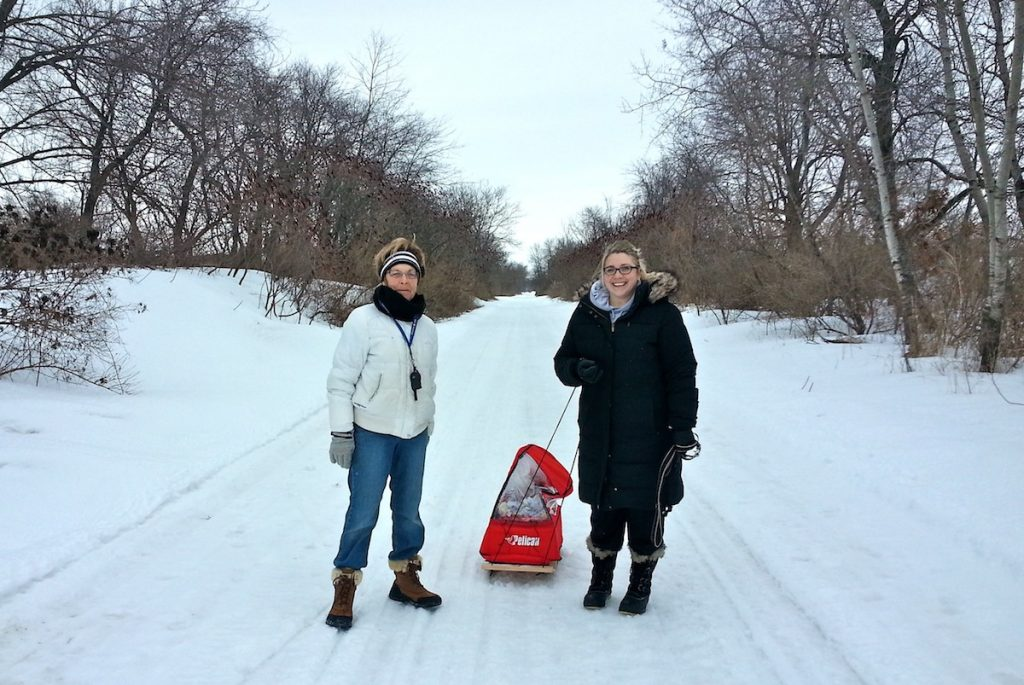 two women pulling a child in a sled on the Badger trail